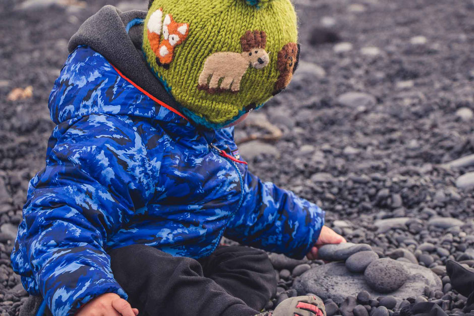 Playing with rocks on Djupalonssandur Beach Snaefellsjoekull National Park Iceland with kids