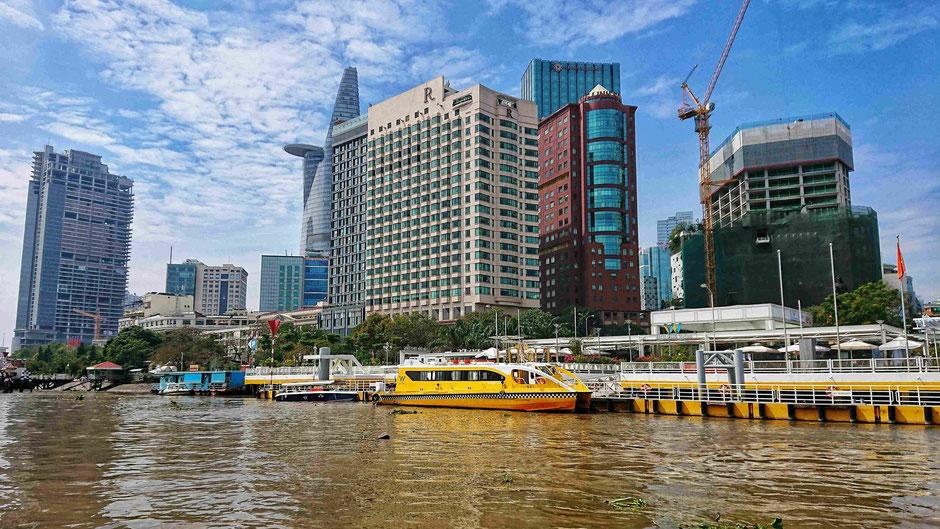 Ausblick vom Saigon River auf den Bach Dang – Schiffsanleger und Hochhäuser im 1. Bezirk von Ho Chi Minh Stadt