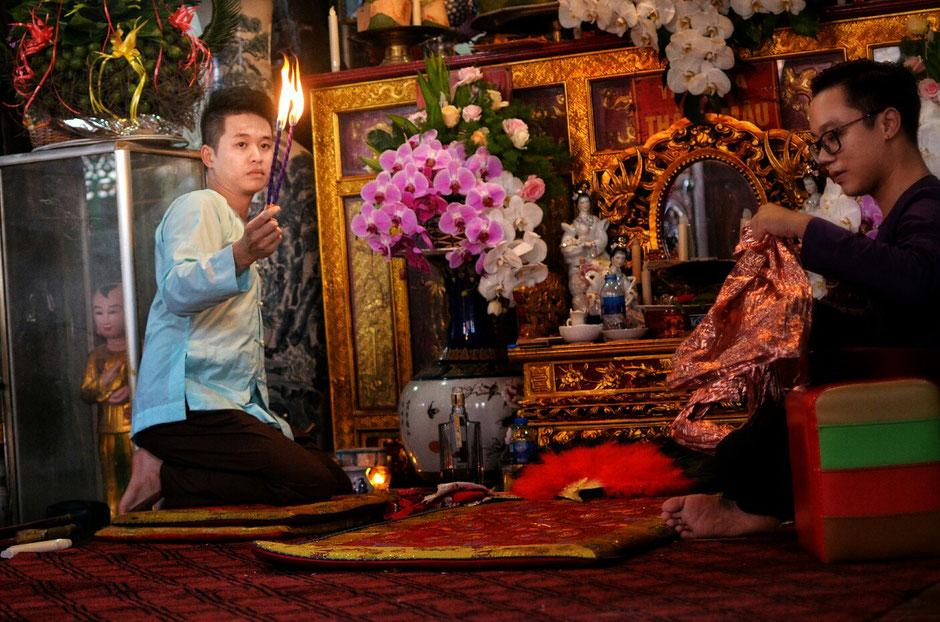 Len Dong – Zeremonie – Altar – geschmückt – Blumen – Gaben für die Geister – zwei Personen - sitzend - Kleidung und Feuer in der Hand