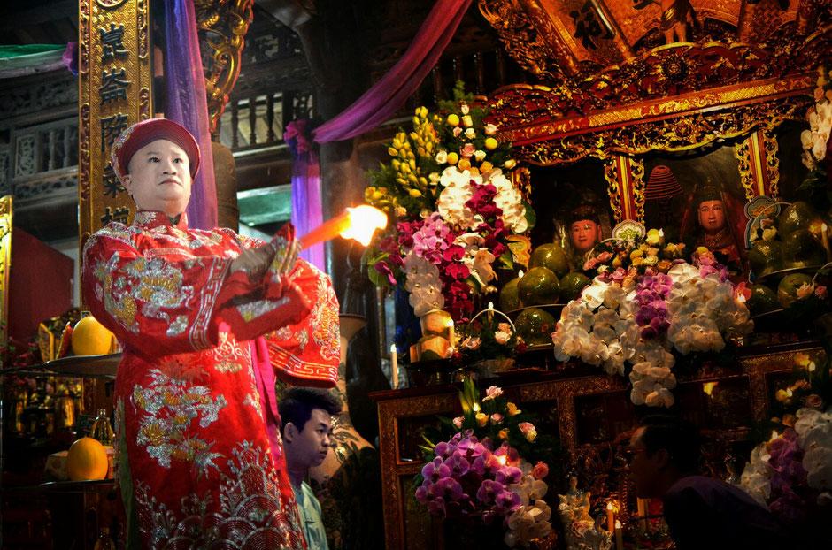 Len Dong – Zeremonie – Altar – geschmückt – Blumen – Gaben für die Geister – Person in prächtig roten Gewand – stehend – Feuerfackel in der Hand