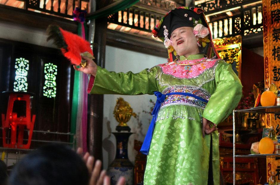Len Dong – Zeremonie – Altar – geschmückt – Blumen – Gaben für die Geister – Person in prächtig grünem Gewand – stehend – roten Fächer in der Hand