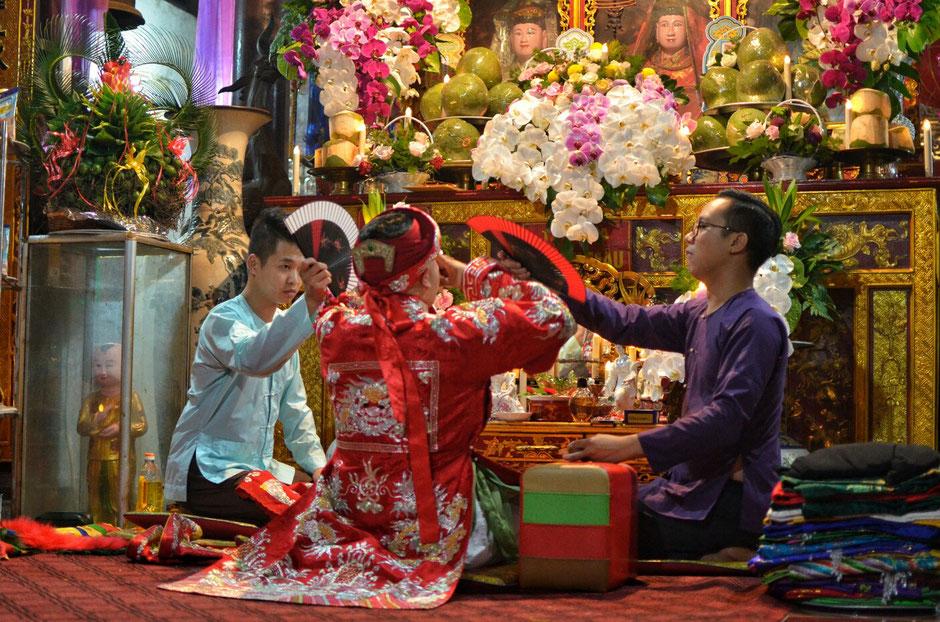Len Dong – Zeremonie – Altar – geschmückt – Blumen – Gaben für die Geister – Person in prächtig roten Gewand – Männer mit Fächern