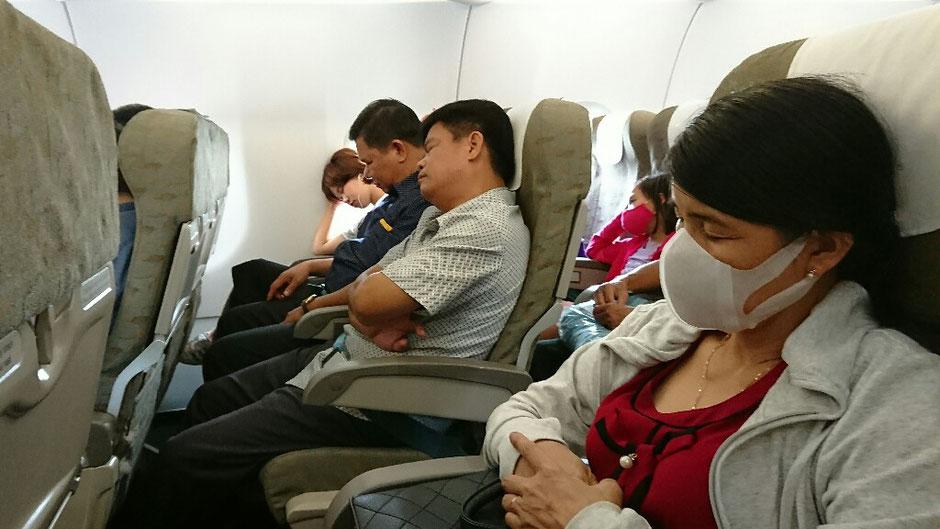 Erkundungstour - zentrales Hochland  - Vietnam – Erkundungstour – Ly und Heiko – Viethouse – im Flugzeug – Vietnam Airlines - Hanoi - Pleiku -  Gesichtsmasken – Frau – schlafen – Mann – Flugzeugsitze