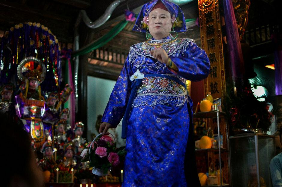 Len Dong – Zeremonie – Altar – geschmückt – Blumen – Gaben für die Geister – Person in prächtig blauem Gewand – stehend
