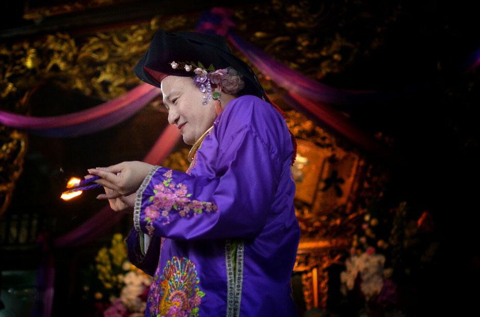 Len Dong – Zeremonie – Altar – geschmückt – Blumen – Gaben für die Geister – Person in prächtig blauem Gewand – stehend – Feuer in der Hand