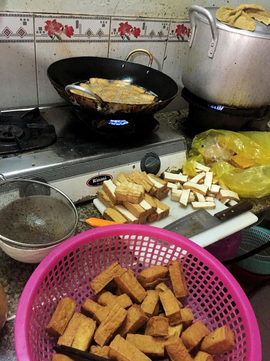 Blick in eine vietnamesische Garkueche, hier wird Tofu vorbereitet, geschnitten und im Wok frittiert