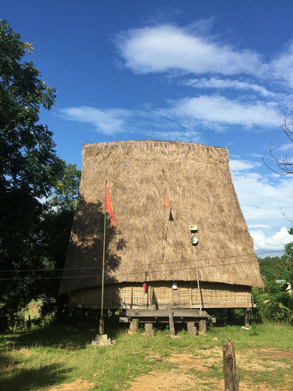 Erkundungstour - zentrales Hochland  - Vietnam – Erkundungstour – Ly und Heiko – Viethouse – Nha Rong - Dorfgemeinschaft – Haus – Gebäude – Dorf – Lautsprecher – Kabel – Strohdach – blauer Himmel – grüne Bäume
