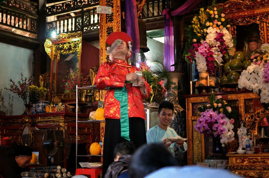 Len Dong – Zeremonie – Altar – geschmückt – Blumen – Gaben für die Geister – Person in prächtig rotem Gewand – wirft Geld – Geldscheine in die Luft