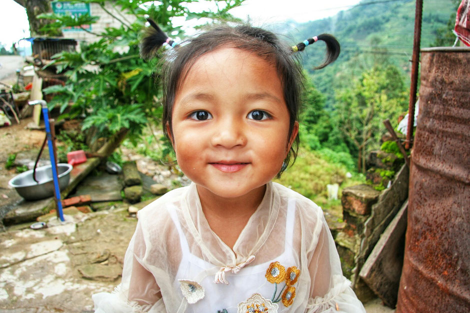 Erkundungstour – Ly und Heiko auf Tour in China – irgendwo in der chinesischen Provinz Yunnan – kleines Mädchen mit Zöpfen