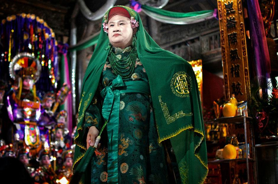Len Dong – Zeremonie – Altar – geschmückt – Blumen – Gaben für die Geister – Person in prächtig gruenem Gewand – stehend –