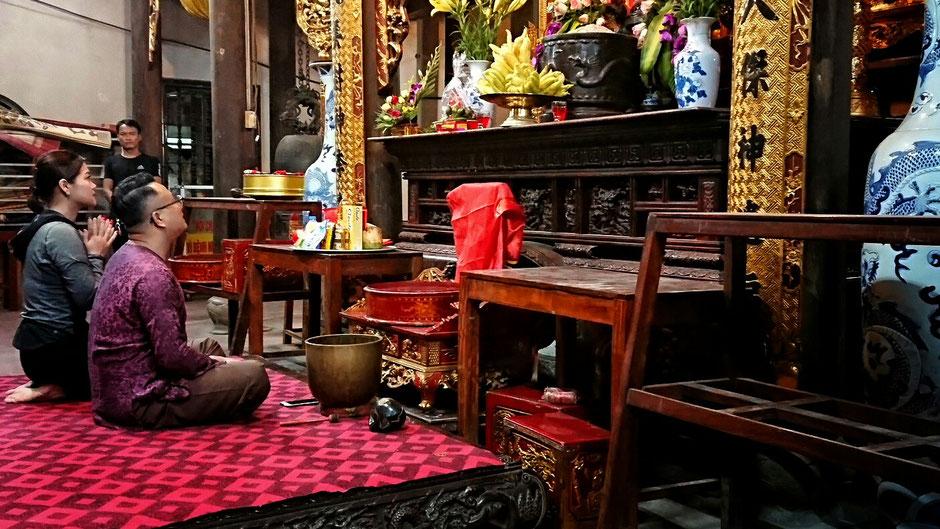 asiatischen Menschen vor einem Altar – halten Andacht – Klangschale und Mobil auf dem Boden liegend
