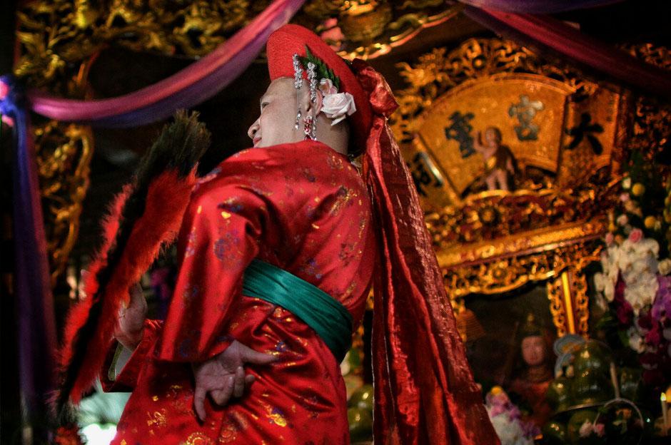 Len Dong – Zeremonie – Altar – geschmückt – Blumen – Gaben für die Geister – Person- Medium - in prächtig rotem Gewand – stehend
