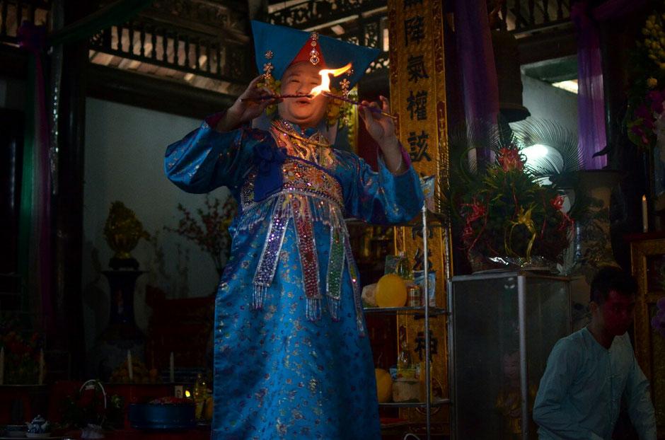 Len Dong – Zeremonie – Altar – geschmückt – Blumen – Gaben für die Geister – Person in prächtig blauem Gewand – stehend – zwei Fackeln in der Hand