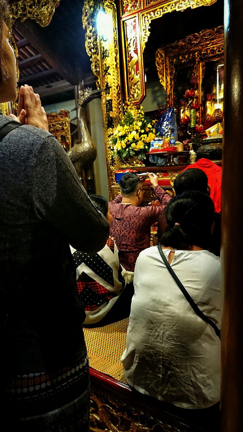 asiatische Menschen vor einem Altar sitzend und stehend – Hände zum Gebet gefaltet – ein Kranich