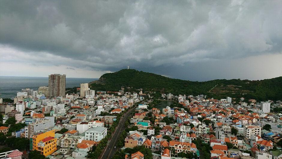 Vung Tau - niemals Winter – Ly und Heiko vom Viethouse in Vietnam - Blick über einen Teil der Stadt am Thuy Van Strand – im Hintergrund die Christus von Vung Tau - eine 32 Meter hohe Statue – Häuser – Meer – tiefhängend graue Wolken