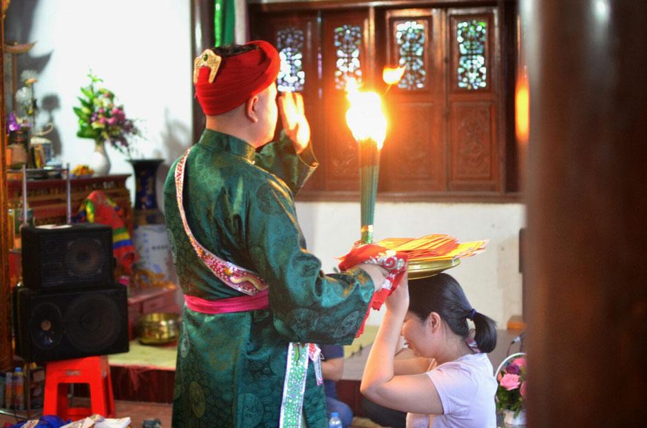 Len Dong – Zeremonie – Gaben für die Geister – Person in prächtig gruenes Gewand – stehend – Feuerfackel in der Hand - Frau kniet