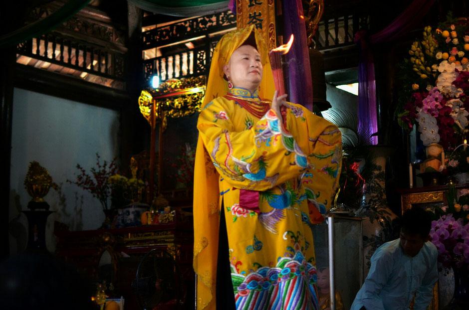 Len Dong – Zeremonie – Altar – geschmückt – Blumen – Gaben für die Geister – Person in prächtig gelb bunten Gewand – stehend – Fackel in der Hand