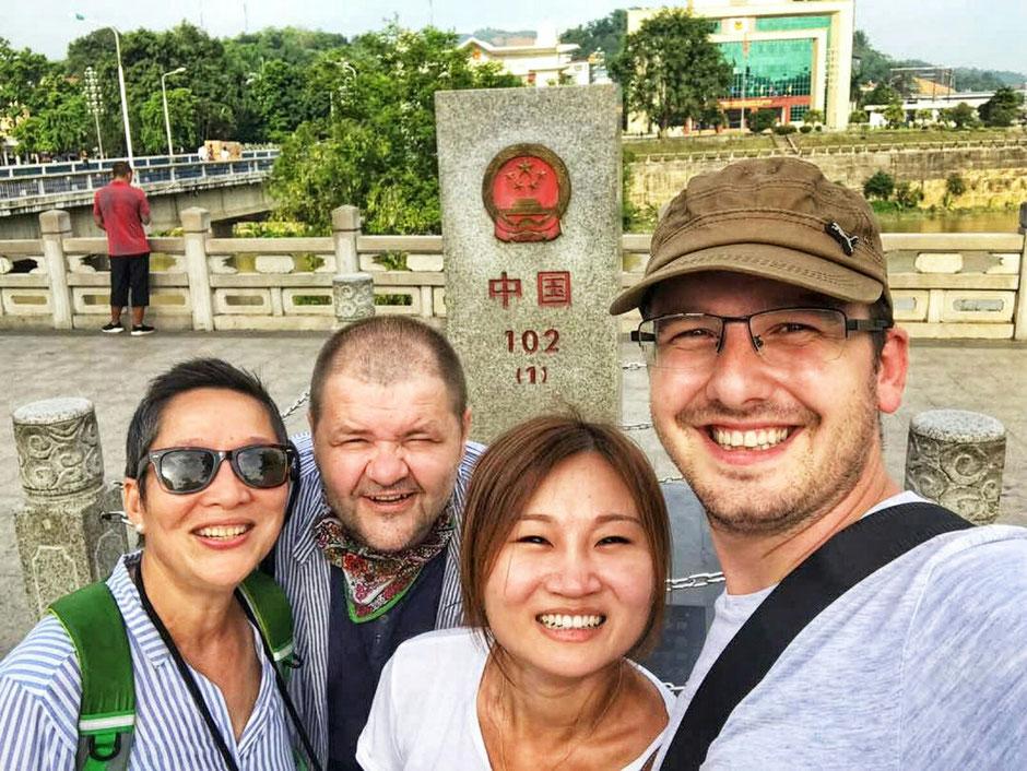 Erkundungstour – Ly und Heiko auf Tour in China – die Reisegefährten – von links nach rechts -  Ly – Heiko – Katie – Alex – hier Grenzstadt Hekou – auf der gegenüberliegenden Seite befindet sich die vietnamesische Grenzstadt Lao Cai – Grenzstein 1 China