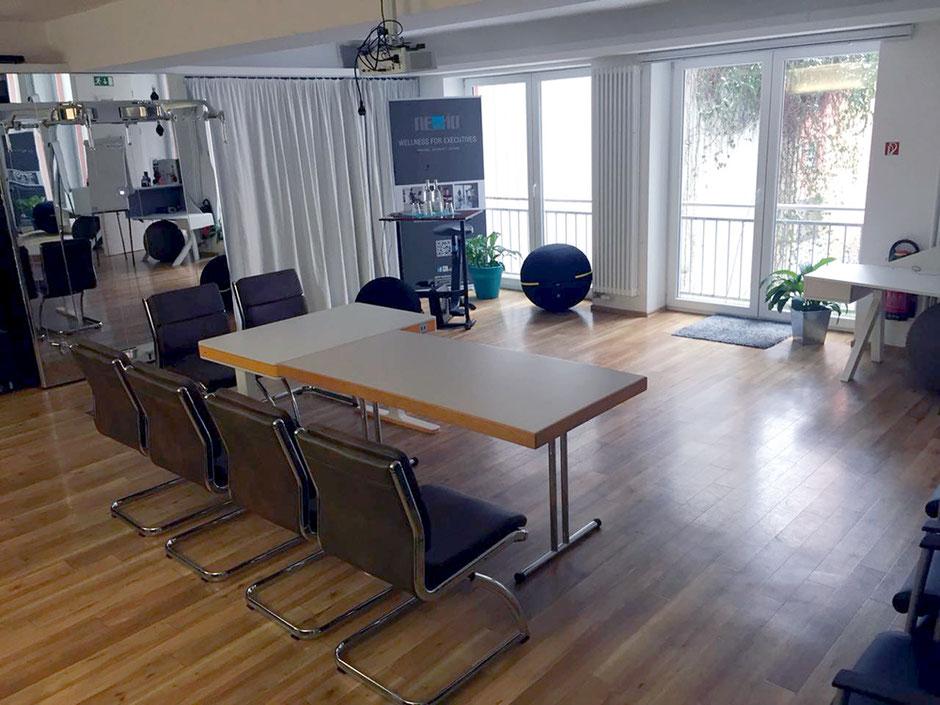 Ansicht eines Veranstaltungsraums mit Tischen, Stühlen und verschiedenen Geräten