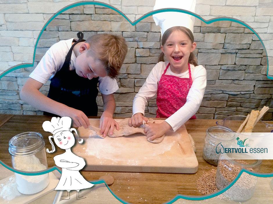 2 Kinder arbeiten mit einem Brotteig vor einer Steinwand und haben Spaß beim Backen lernen