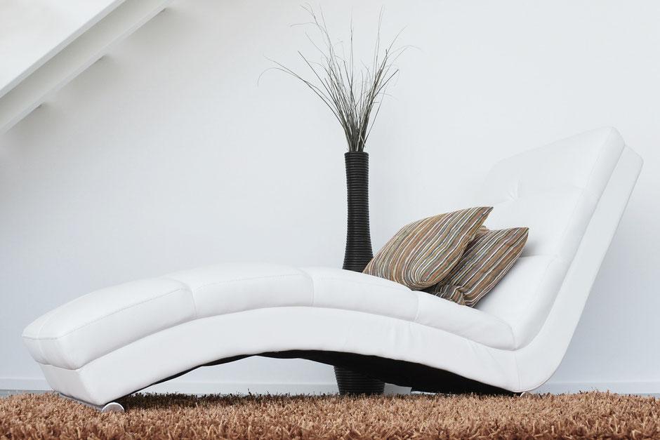 Sofasessel mit zwei Pölstern auf Teppich. Große Vase steht neben Sofasessel.