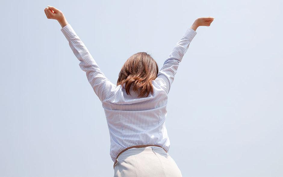 両手を広げて背伸びをする若い女性の後姿