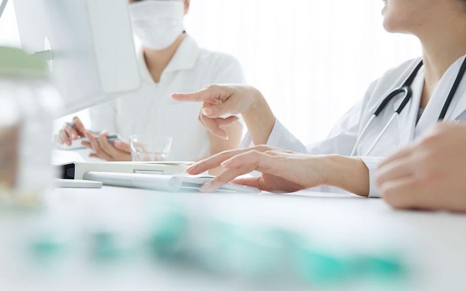 医療機関でPCを見ながら打合せ中の看護師