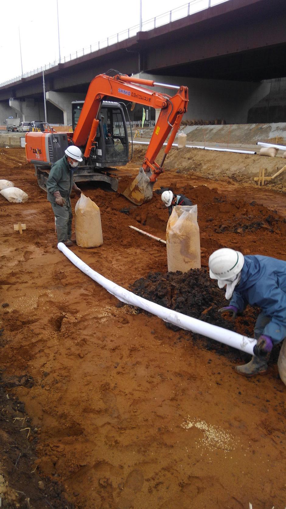 暗渠の施工で、掘削時に暗渠パイプとモミガラを用意する様子です。