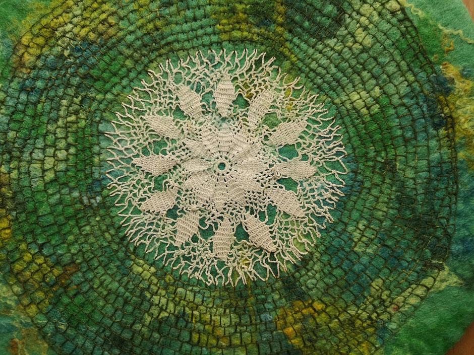 Detail eines handgefilzten, bestickten Kissens in Grüntönen mit aufgefilzter Häkelspitze