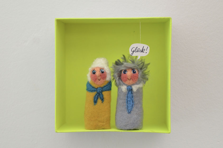 handgefilzte Fingerpuppen von Faserverbund in einer Box aus Karton, Oma und Opa mit Sprechblase Glück