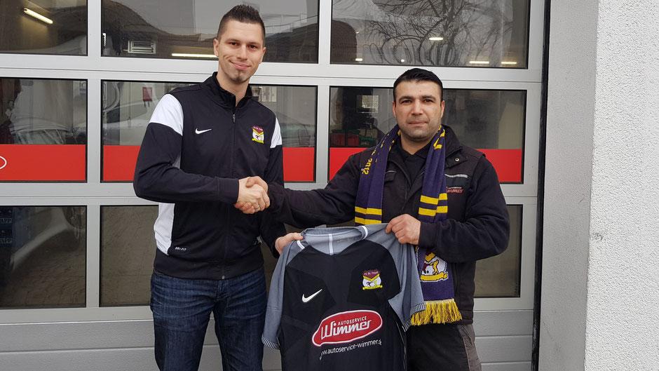 Fouli-Manager Florian Weiß (l.) übergibt Mehmet Celik ein Exemplar des neuen Fouli-Trikots, sowie einen Fan-Schal. Künftig wird es im Büro des Autoservice Wimmer hängen.