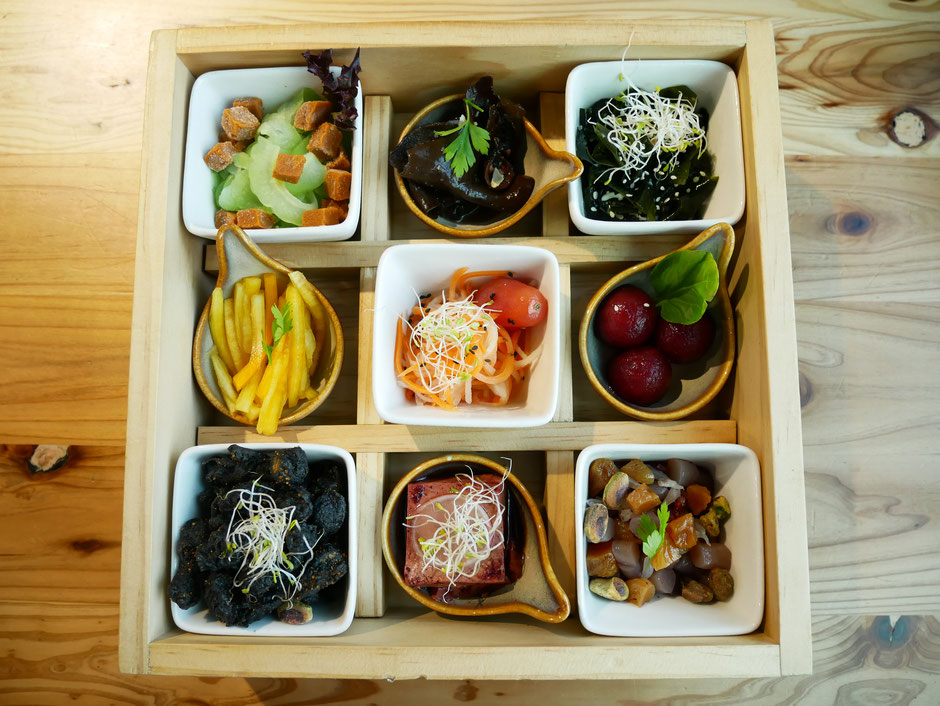 9 different vegetarian dishes in served in a bento box that has been compartmentalised