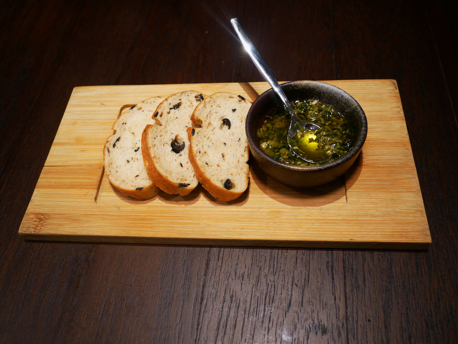 Three slices of gluten free olive bread with a pesto sauce