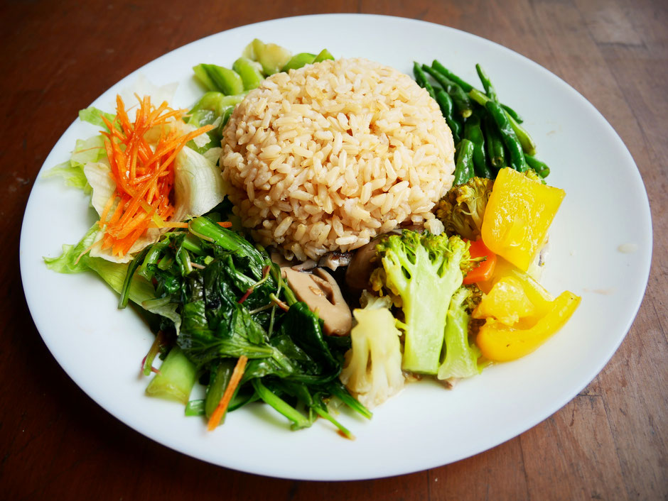 Organic brown rice with different types of chinese vegetables served on a simple white porcelain plate on a wooden table