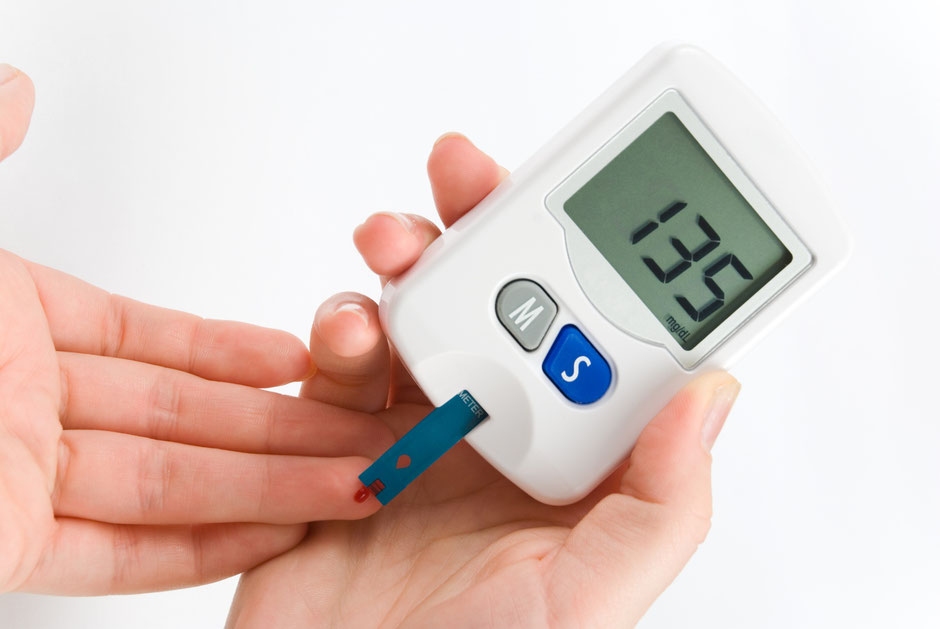 A picture of someone pricking their finger to check for blood sugar levels with the insulin device