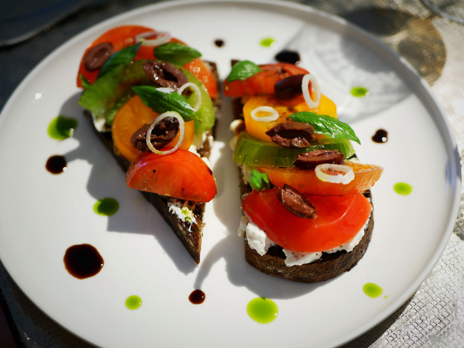 Heirloom tomatoes, burrata, olives and basil served on bread at Como Cuisine Singapore