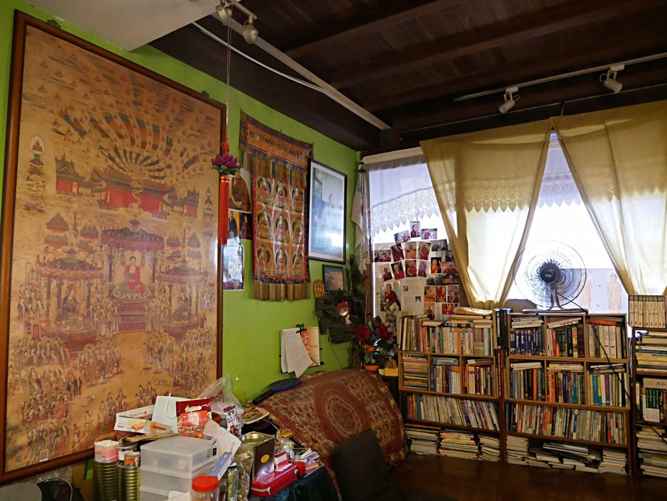 A small breathing decorated with buddhist motif, some books, a fan and a supportive cushion