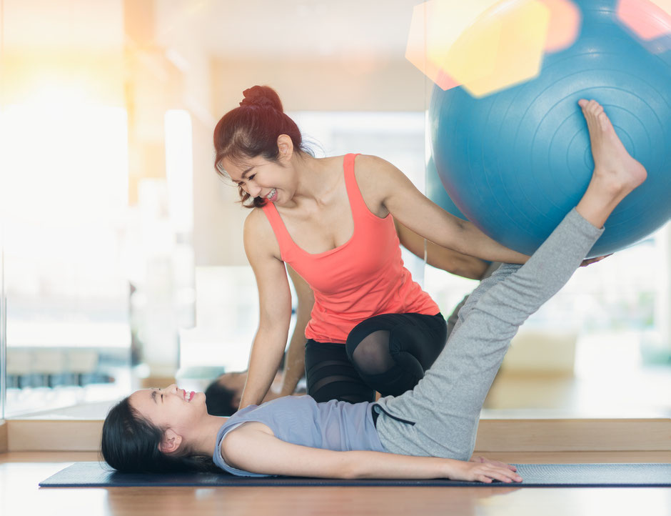 A female personal trainer assisting her female client in performing a corrective exercise with a swiss ball