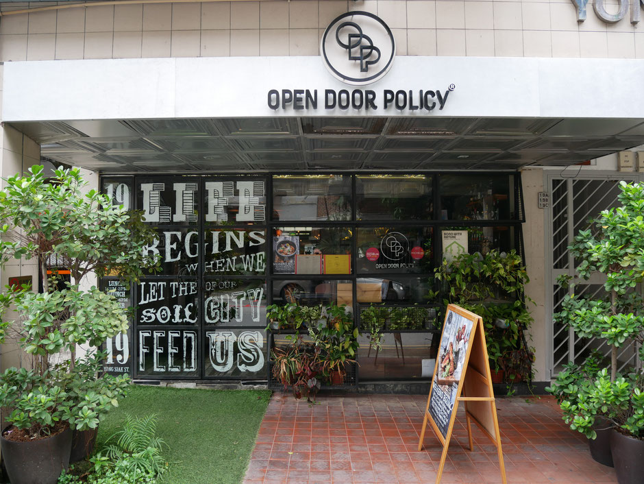 The entrance of  Open Door Policy along Yong Siak street is filled with plants and graphic work