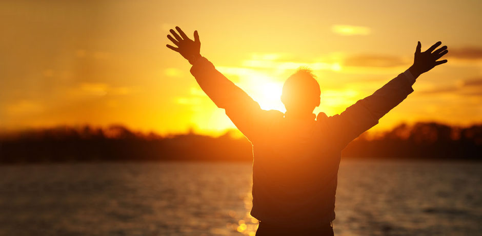 A silhouette of a man with his hands outstretched embracing the view of the sunrise