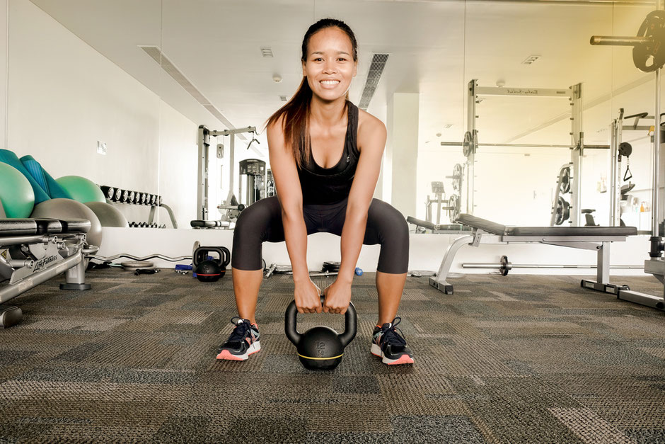 A happy asian woman doing a kettlebell exercise at the gym