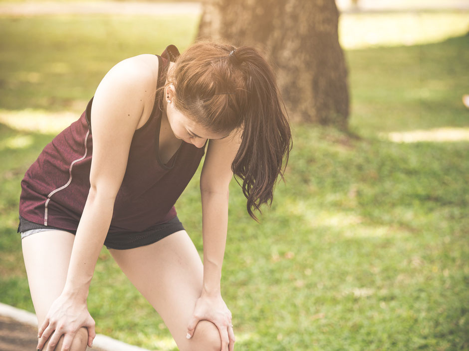 Woman at the park with her body bent forward and hands on her knees is exhausted from running