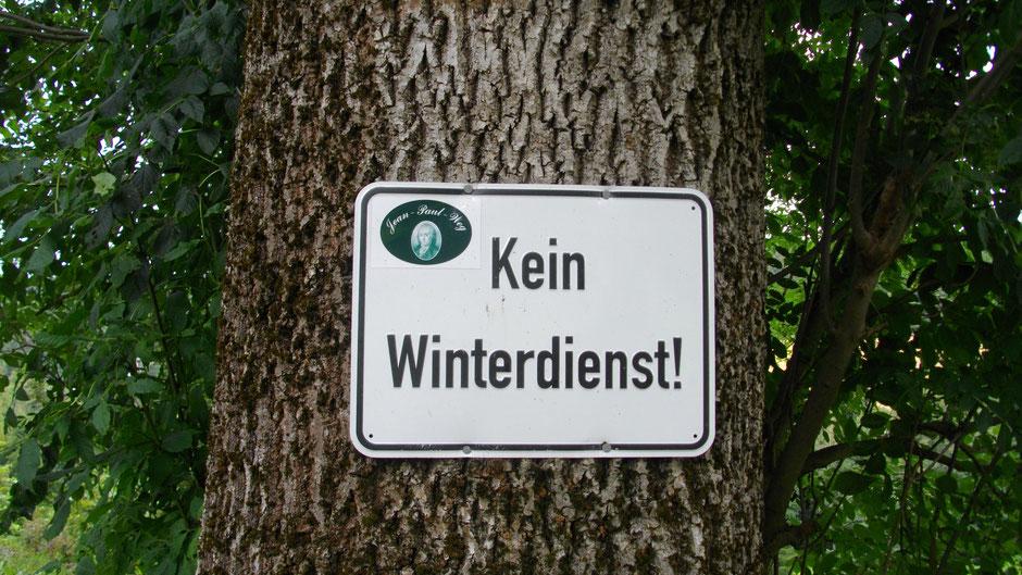 """Jean-Paul-Weg Wegmarkierung auf einem Baumstamm mit dem Schild """"Kein Winterdienst"""""""