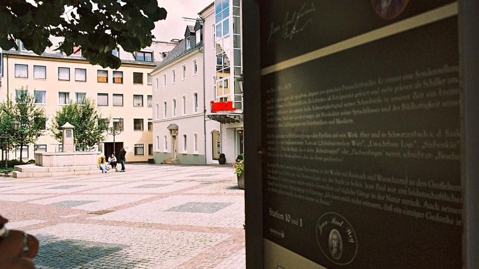 Hinten der Jean-Paul-Brunnen auf dem Schlossplatz in Hof, vorne Stationstafel 10 und 1