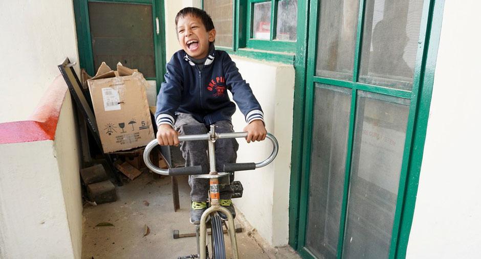 Lachendes Kind auf scheinbar selbstgebautem Heimtrainer