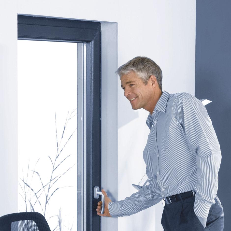 Frau öffnet neu eingebautes Fenster mit Einbruchschutz