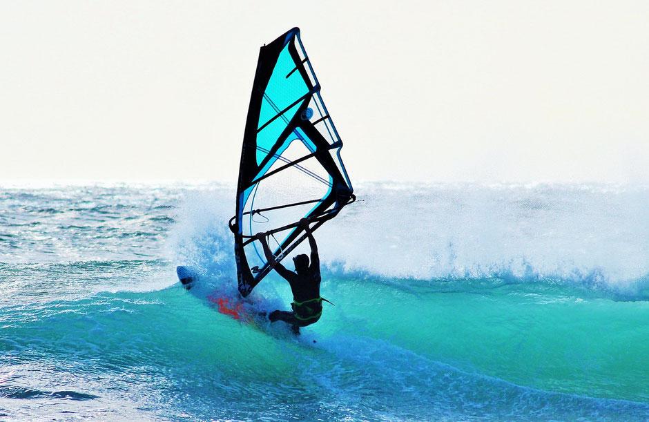 Wie auf einer Stresswelle, surft ein Mann auf einer großen Welle im Meer.