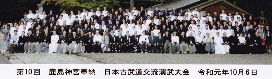 本部役員・来賓・奉納演武者が本殿お側に勢揃い!中央少し左の白い稽古着黒い袴で白髪の男は誰?