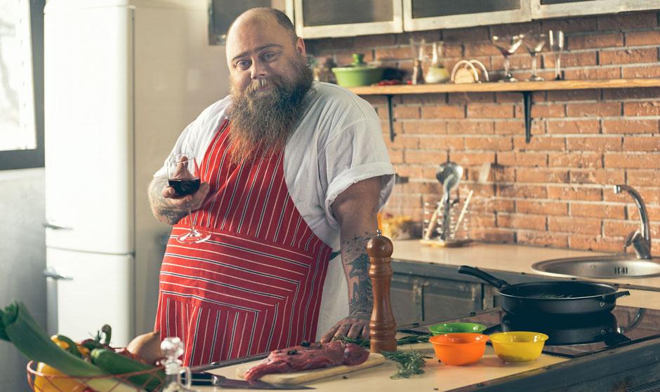 Gicht-Ursachen: Dicker Mann in Küche mit Weinglas und Fleisch
