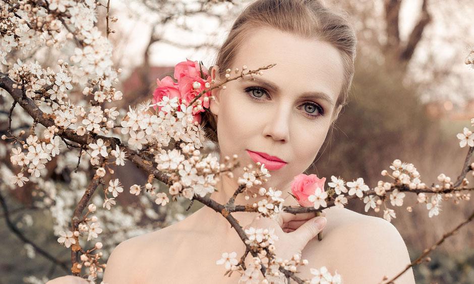 Frauenportrait mit pinken Rosen zwischen weißen Apfelbaumblüten